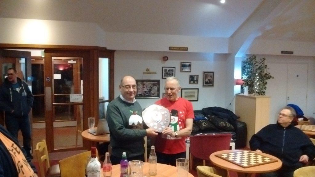 Bob receives the winner's trophy